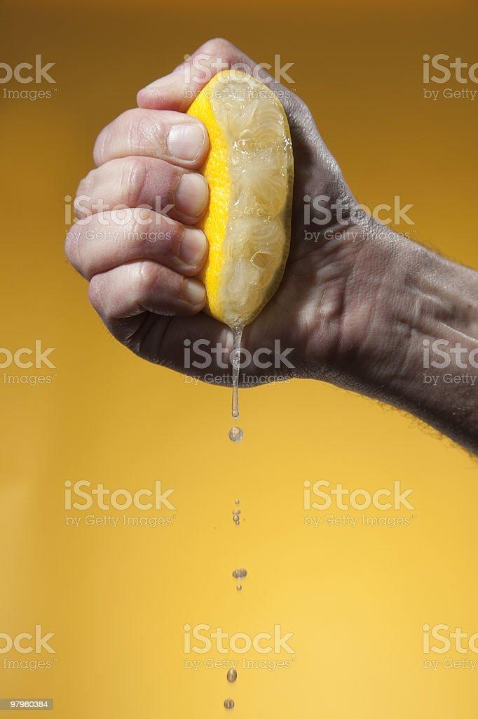Man's hand squeezing half of lemon royalty-free stock photo
