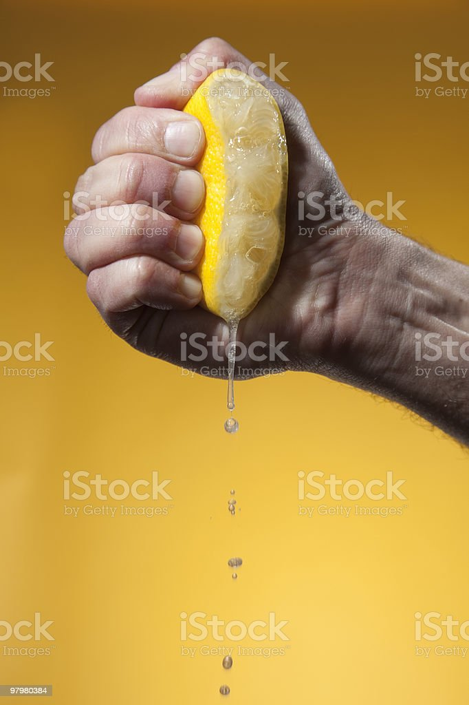 Man's hand squeezing half of lemon stock photo