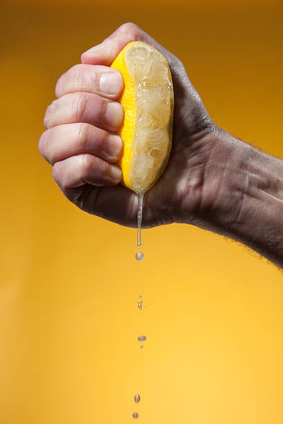 man's hand squeezing half of lemon - squeezing stock pictures, royalty-free photos & images