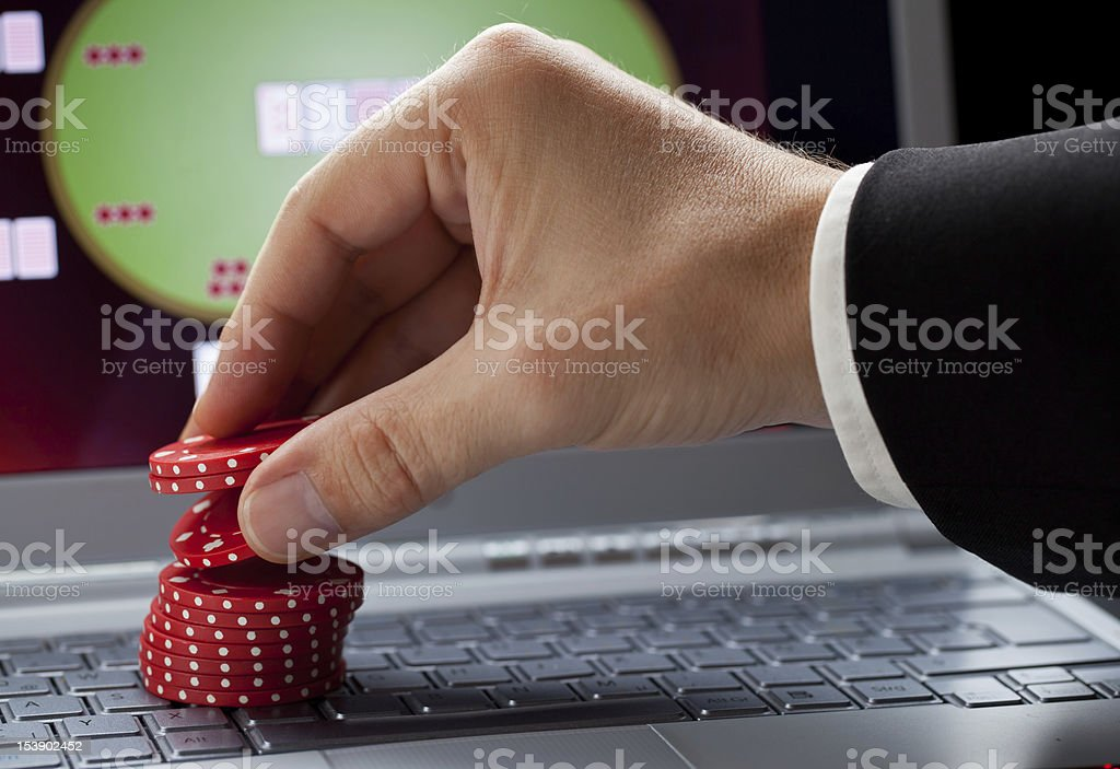 Man's hand stacking casino chips on laptop keyboard royalty-free stock photo