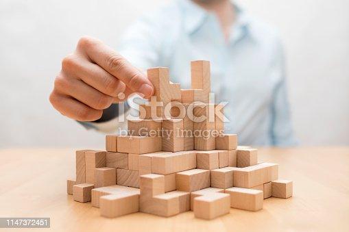 Man's hand stacking wooden blocks. Business development concept
