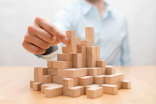 Man's hand stacking wooden blocks. Business development concept stock photo