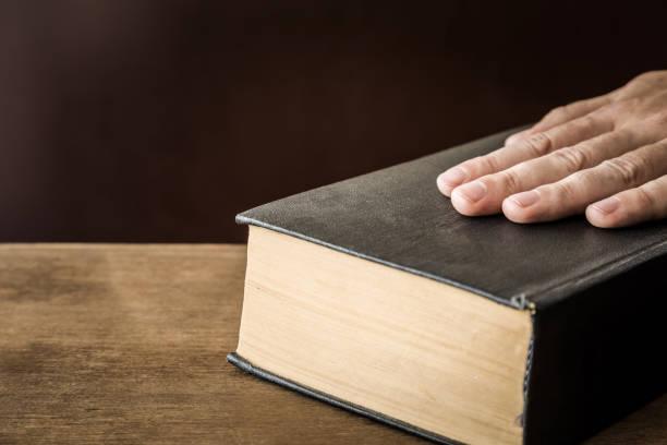 die hand des menschen schwören auf die bibel. eine vereidigung. - eid stock-fotos und bilder