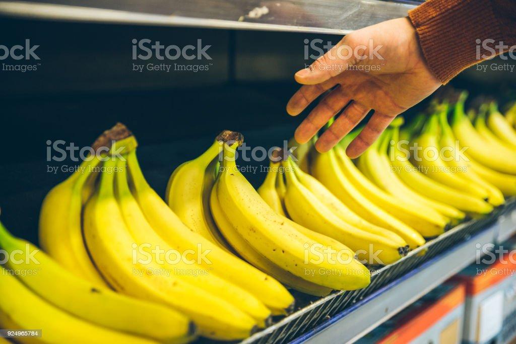 mans hand take bananas from shelf of store stock photo