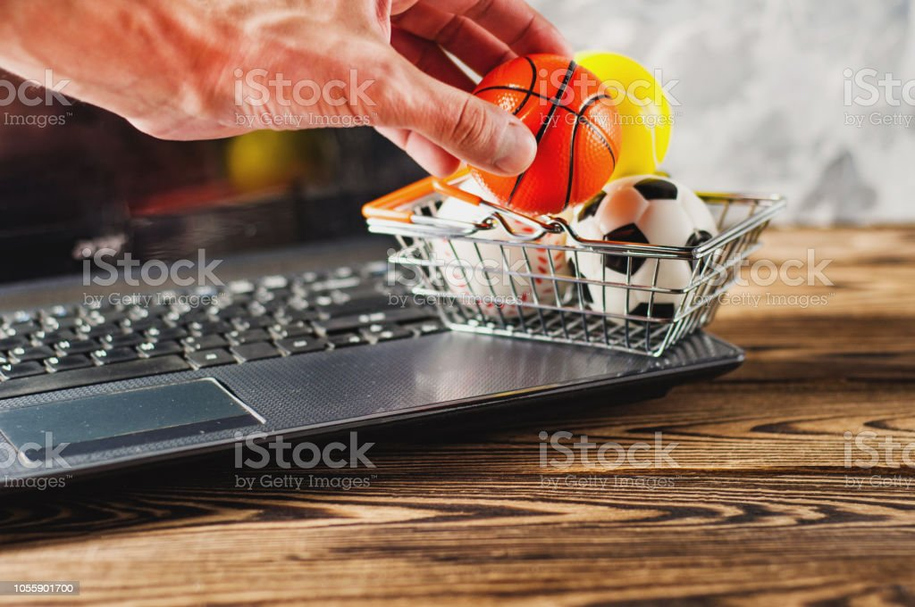 Man\'s hand takes ball with market basket and old dirty laptop on...