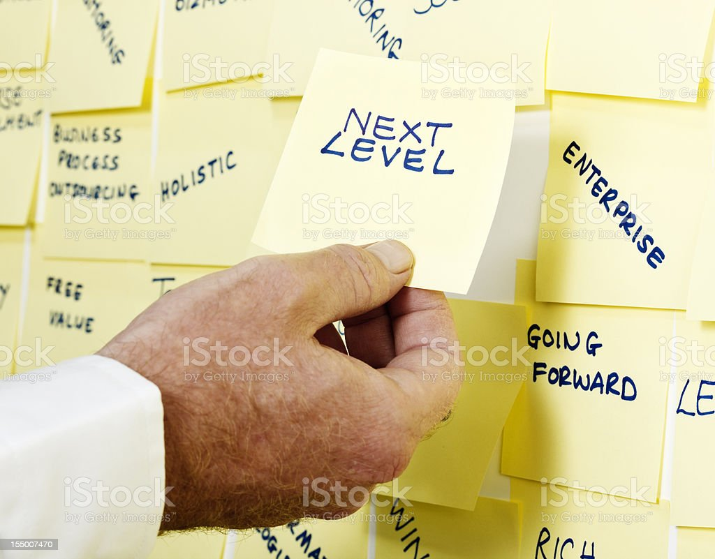 Man's hand takes note 'Next Level' from packed buzzword noticeboard royalty-free stock photo