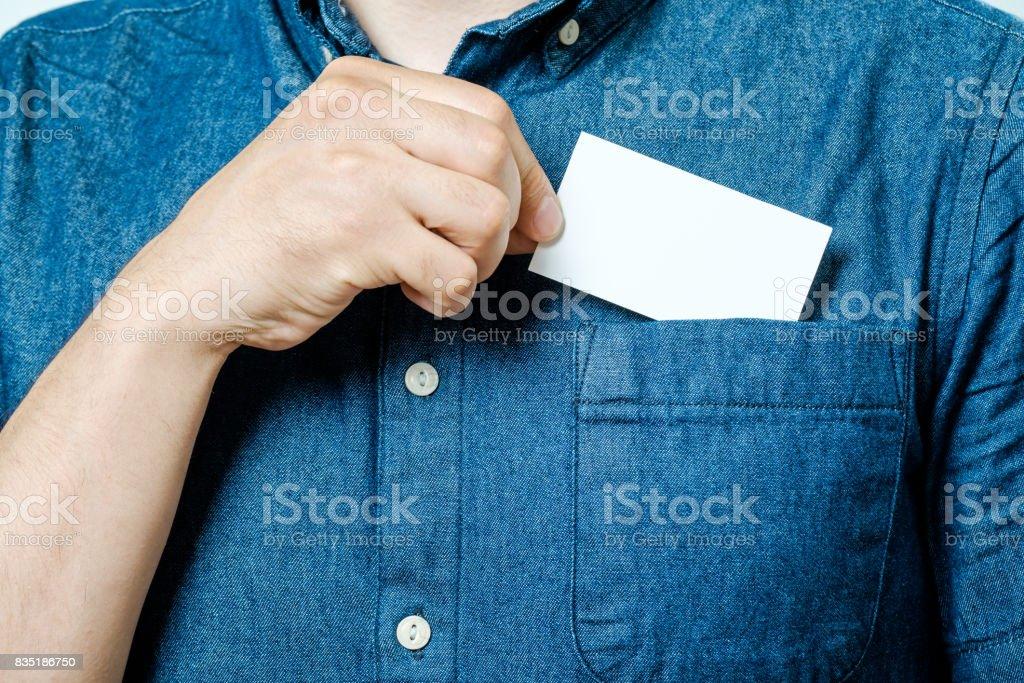 Mano del hombre lleva a cabo en blanco tarjeta de visita del bolsillo de la camisa azul - foto de stock