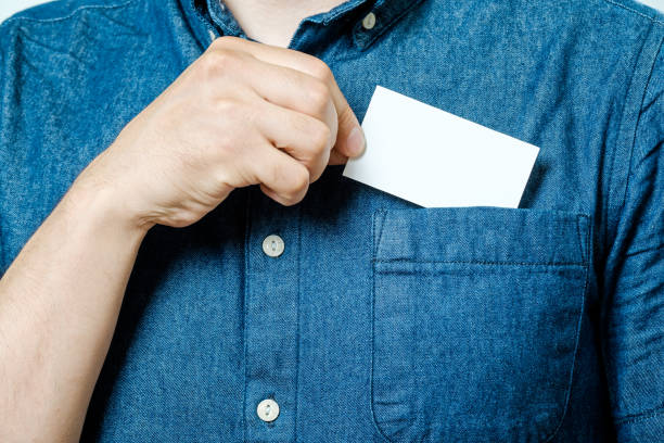 man's hand takes out blank business card from the pocket of blue shirt - pocket stock photos and pictures