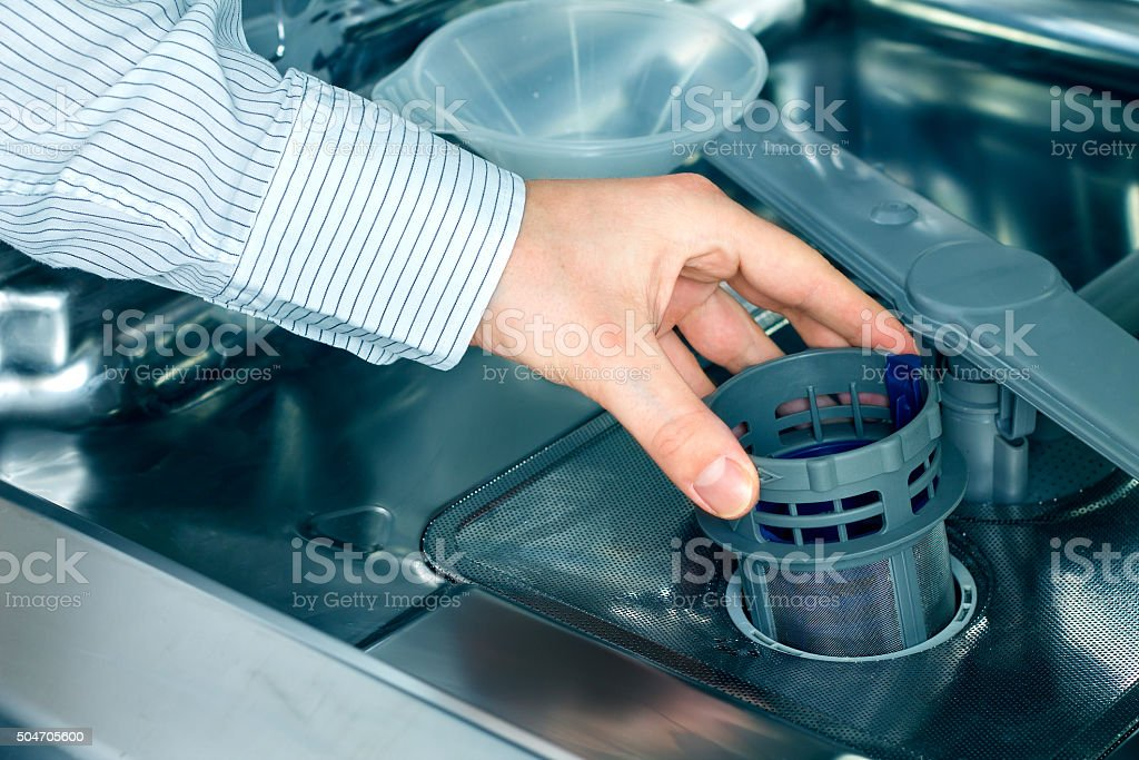 Man's hand taking out a dishwasher filter stock photo