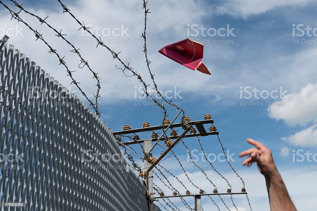 man's hand throwing his passport as a paper airplane over stock photo