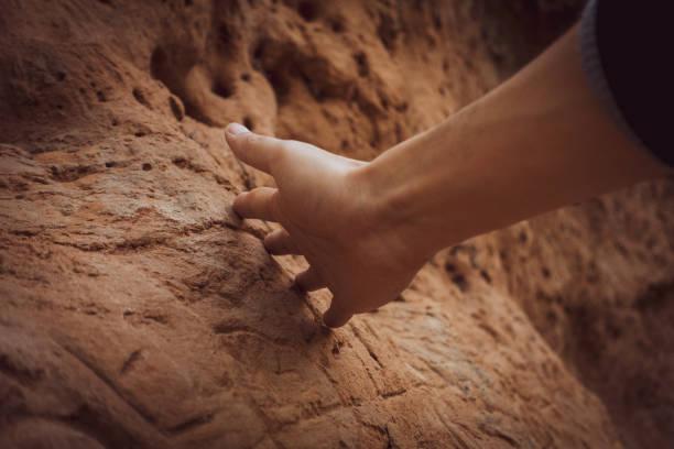 Die Hand des Menschen berührt eine alte Wand – Foto