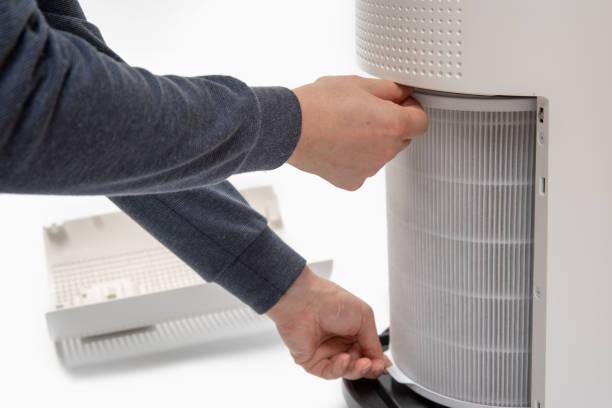 die hand eines mannes macht einen luftreinigungsfilter in einen neuen. - luftfilter stock-fotos und bilder