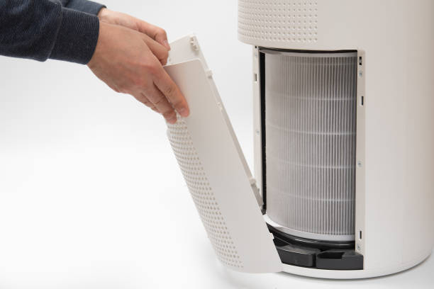 A man's hand turning an air purifier's filter into a new one. stock photo