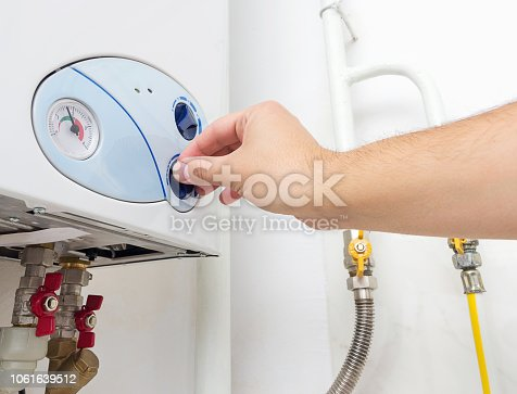 996279800istockphoto Man's hand turning the knob of gas boiler. Heating system at home. 1061639512