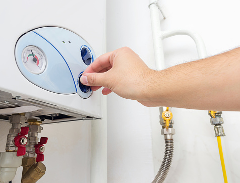 istock Man's hand turning the knob of gas boiler. Heating system at home. 1061639512