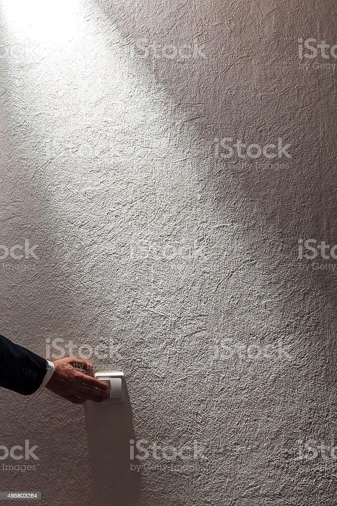 Man's hand turns off the light stock photo