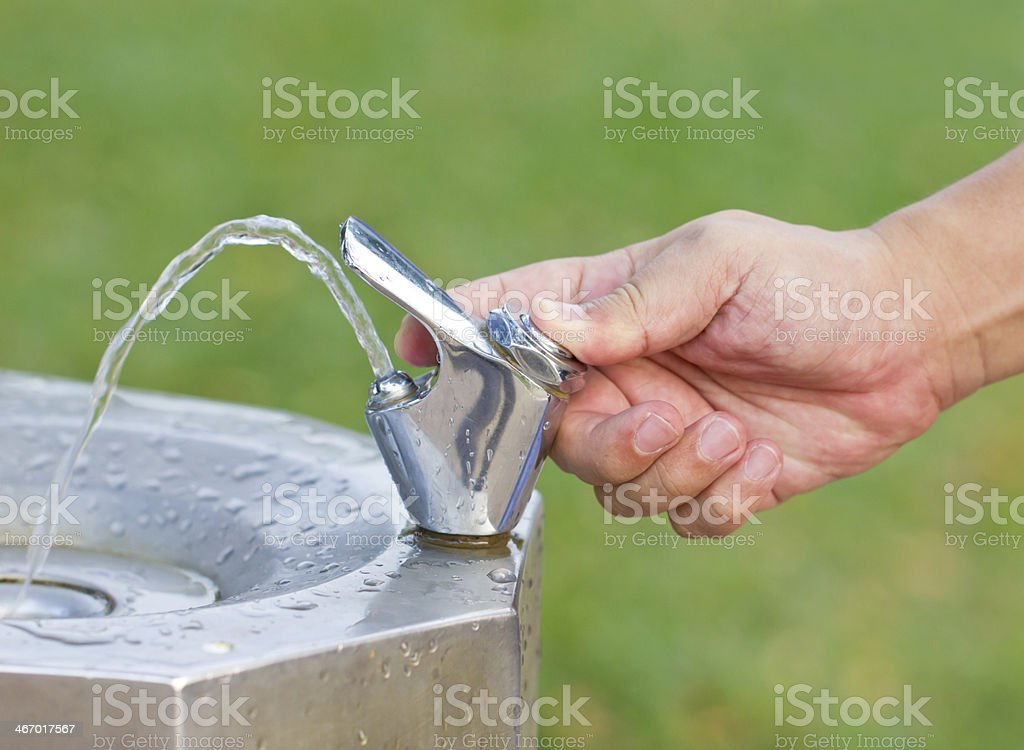 Man's hand turns on the drinking water faucet. royalty-free stock photo