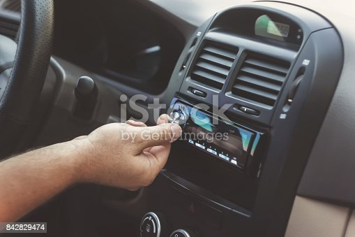 istock man's hand twists the volume in a retro toning car 842829474