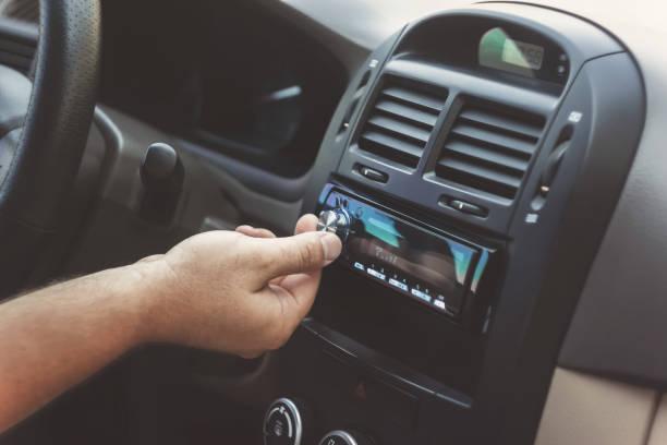 man's hand twists the volume in a retro toning car - radio foto e immagini stock