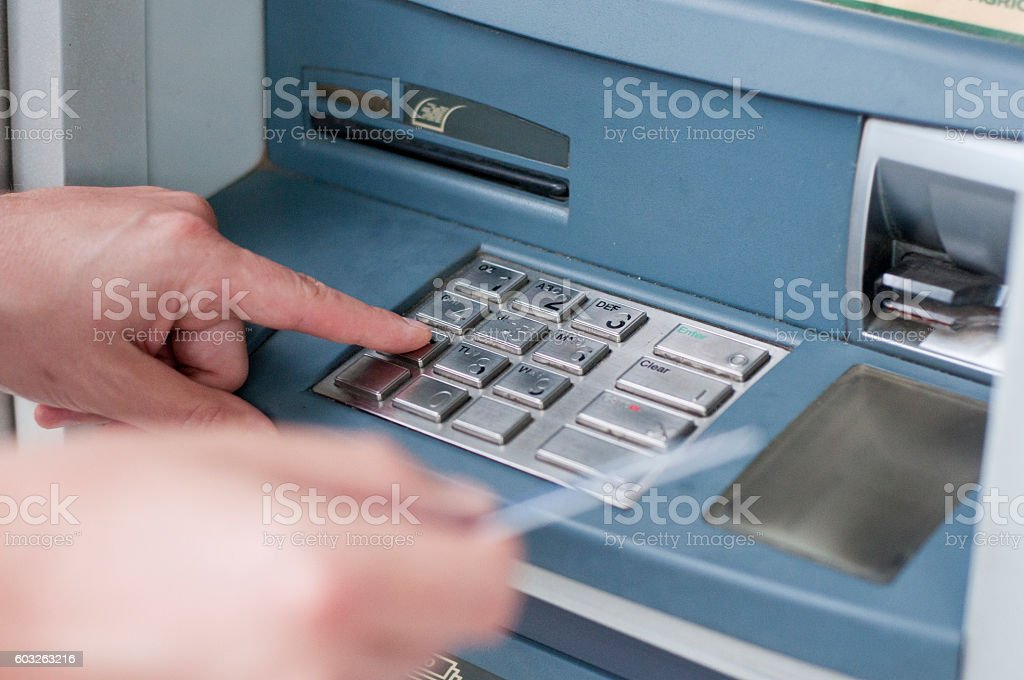 Man's Hand Using Card To Withdraw Money. ATM entering pin stock photo