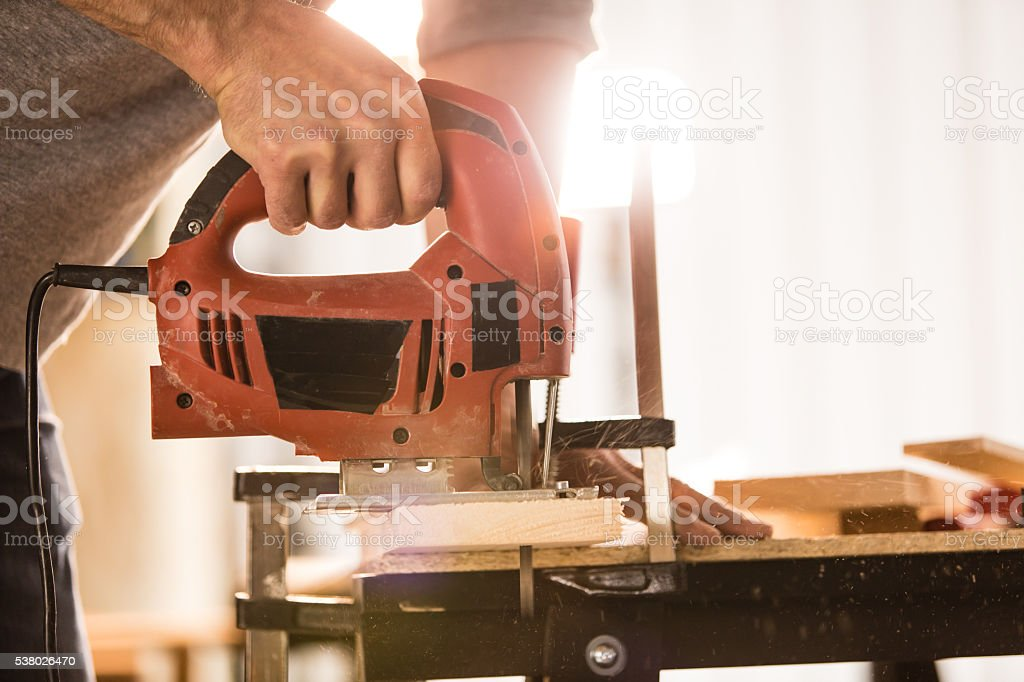 Man's hand using electric jigsaw stock photo