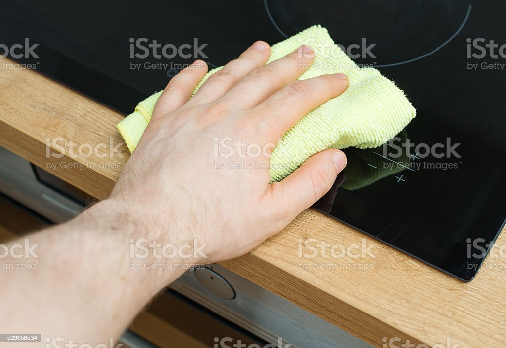 Man's hand wipes cooktop in the kitchen. stock photo