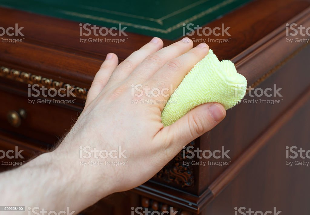 Man's hand wipes dust from antique furniture. stock photo