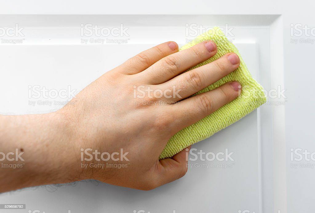 Man's hand wipes dust from white furniture. stock photo