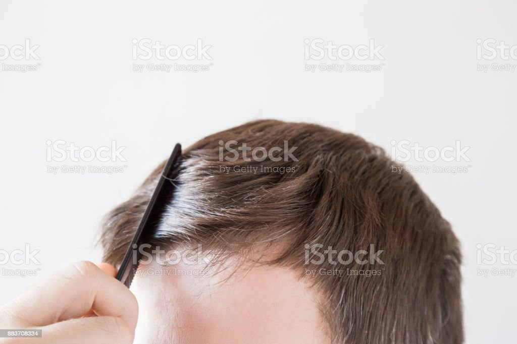 Man's hand with comb brushing his dry brown hair on the gray background. Cares about a healthy and clean hair. Beauty salon concept. stock photo
