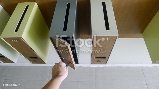 istock Man's hand with key unlocking a post box.close-up view 1136205497