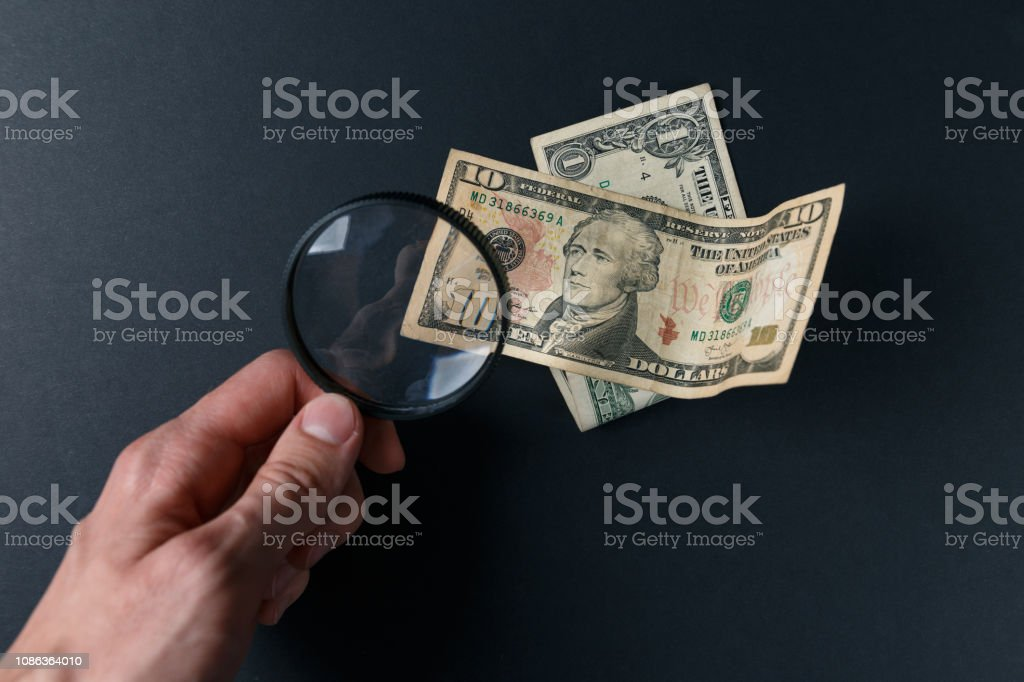 Man\'s hand with magnifying glass and money on black background. Paper...