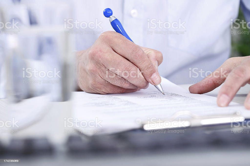 Man's  hand with pen signing document stock photo