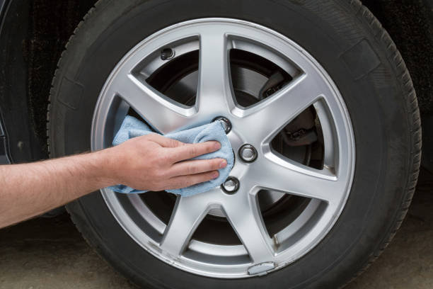 Man's hand with rag cleaning a dusty car wheel disk in the garage. Early spring washing or regular wash up. Professional car wash by hands. stock photo