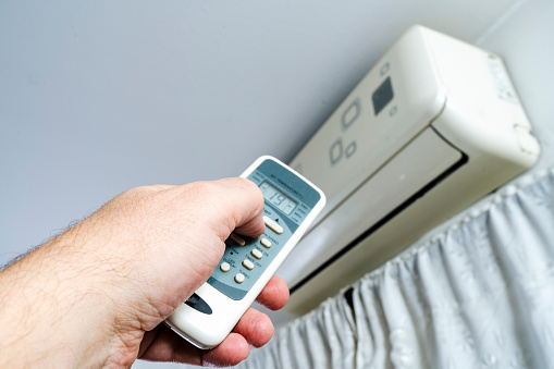 A man's hand with the remote control of an air conditioner.