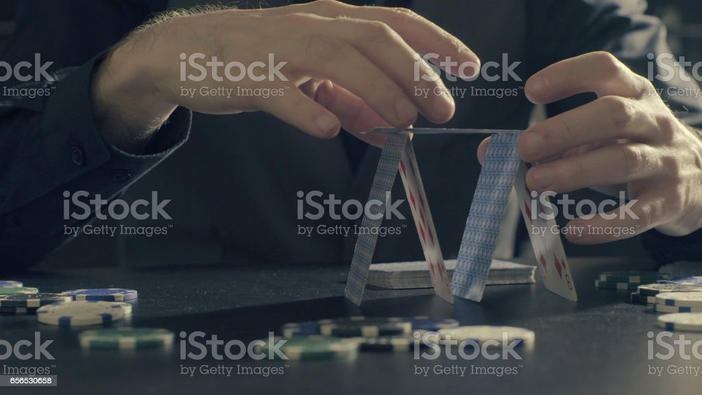 Man's hands building a house of a playing cards stock photo
