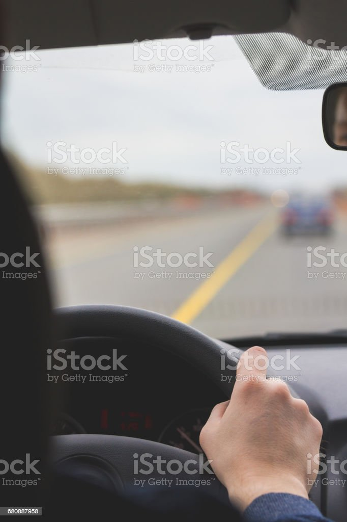 Man's hands for a wheel - inside a car at highway royalty-free stock photo
