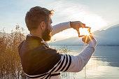 Man's hands frame sunset over mountain lake