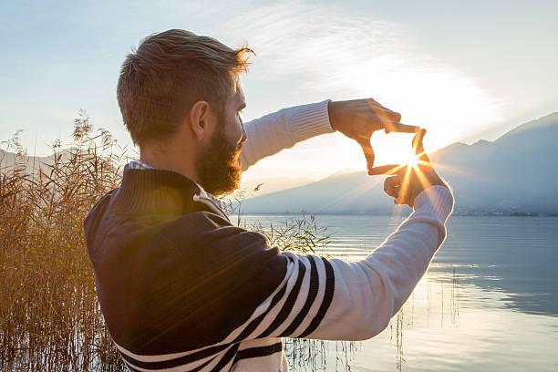 Mann Hand-frame Sonnenuntergang über mountain lake – Foto