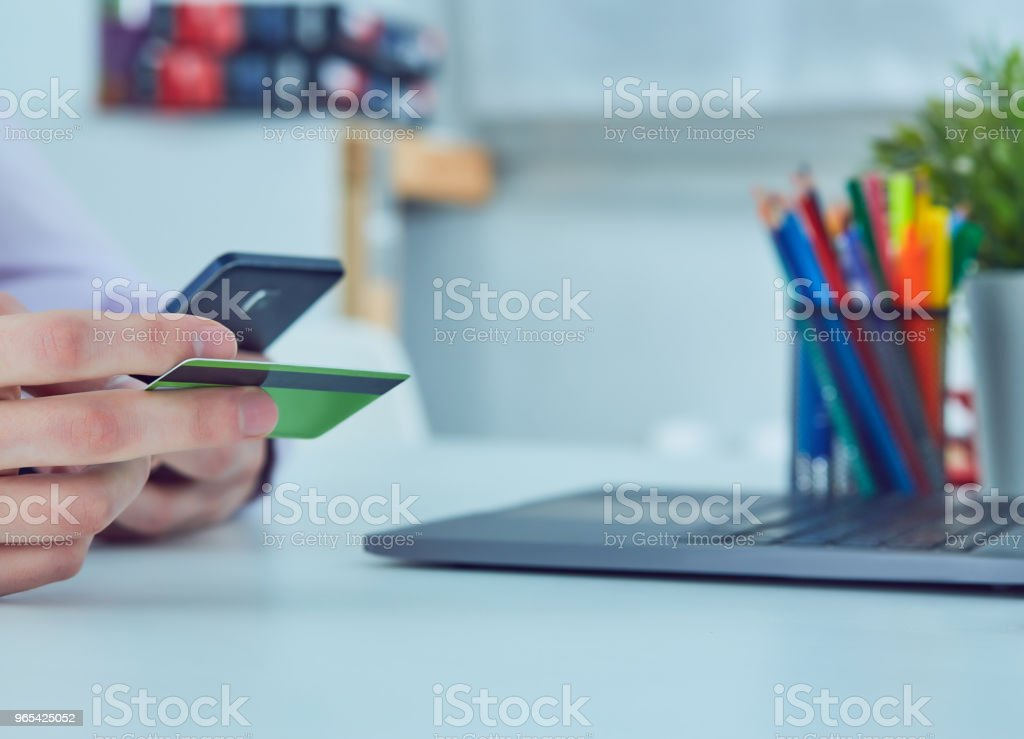 Man's hands holding a credit card and using smart phone for online shopping. Online payment zbiór zdjęć royalty-free