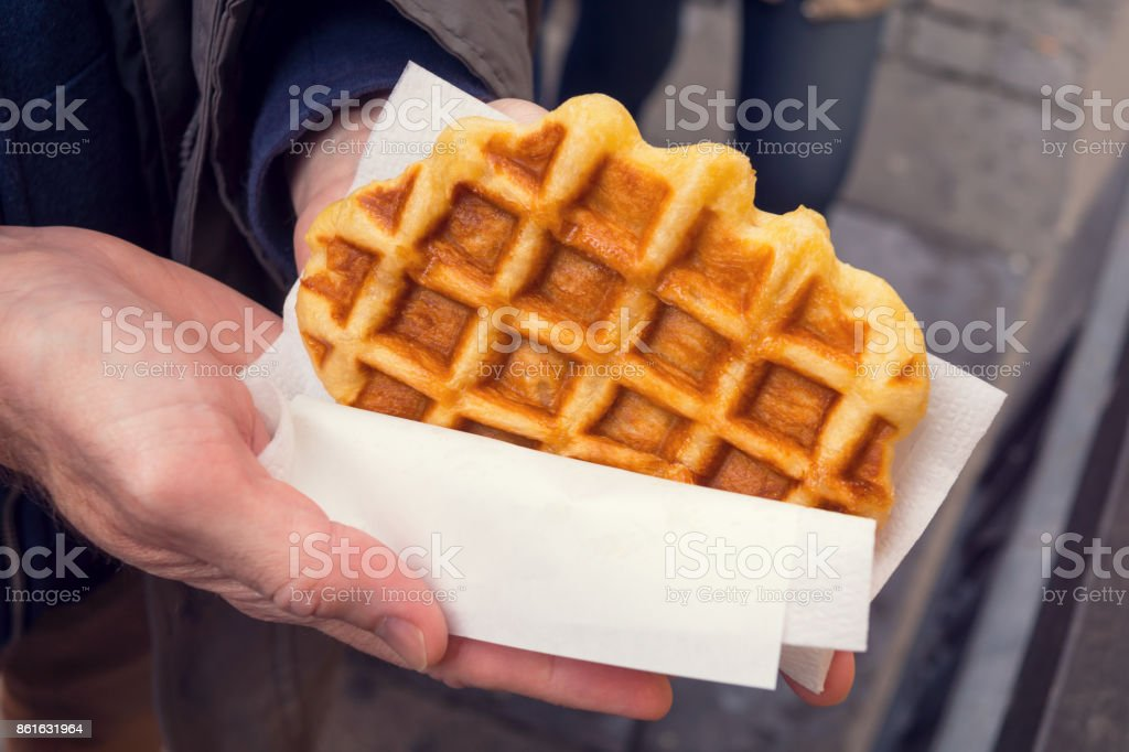 Man's Hands Holding a Liege Style Belgian Waffle Wrapped in Paper stock photo