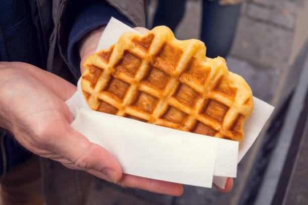 Man's Hands Holding a Liege Style Belgian Waffle Wrapped in Paper A man's hands are holding a fresh and warm Liege style Belgian waffle wrapped in white paper. lulik stock pictures, royalty-free photos & images