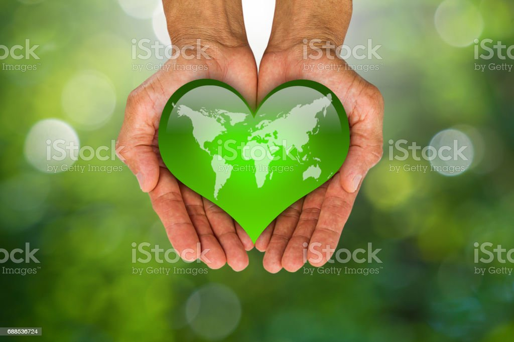 World Map On Hands.Mans Hands Holding Green Heart With World Map On Blurred Green Bokeh