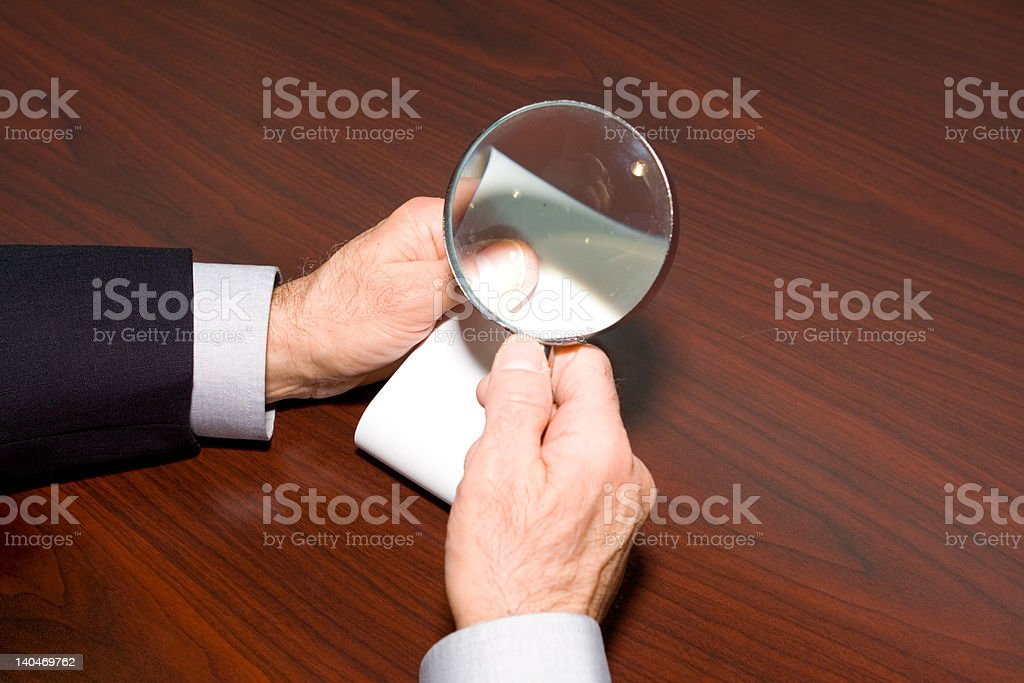 Man's Hands Holding Magnifying Glass Looking at Adding Machine Tape royalty-free stock photo