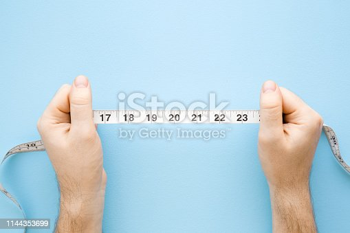 istock Man's hands holding white measure tape on pastel blue background. Mock up for body slimming, weight loss or dressmaker's offer or other ideas. Closeup. Point of view shot. Empty place for text. Top view. 1144353699