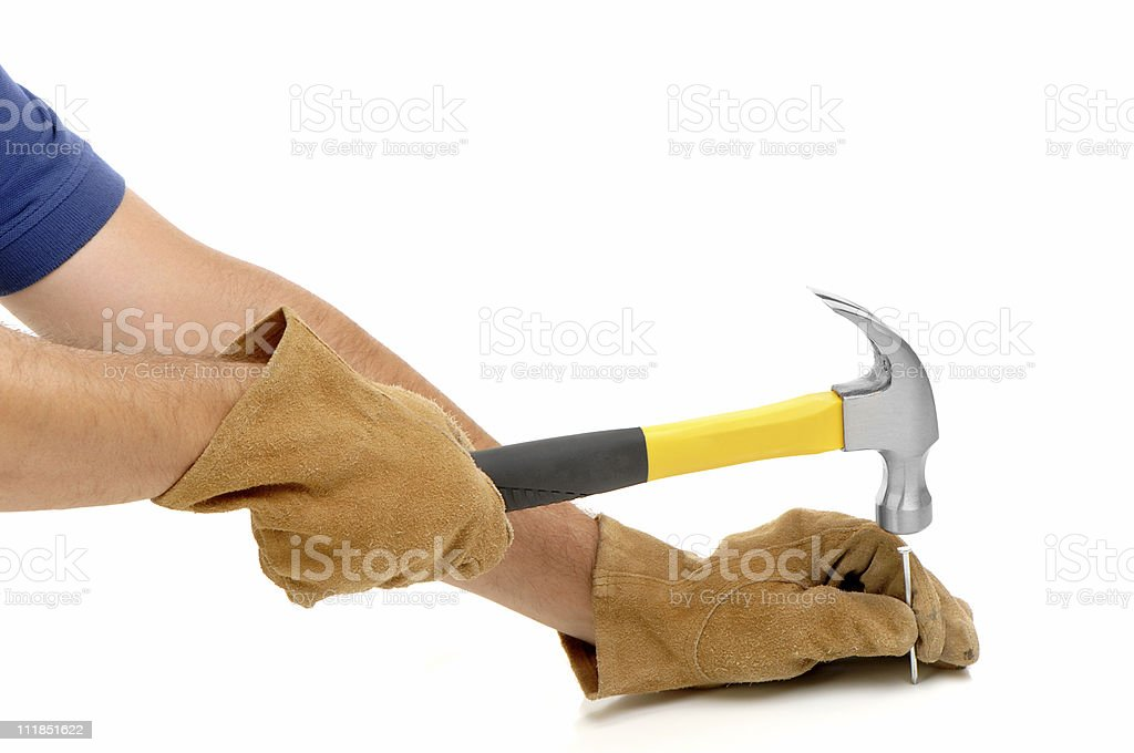 Man's Hands in Gloves Driving Nail with Hammer on White royalty-free stock photo