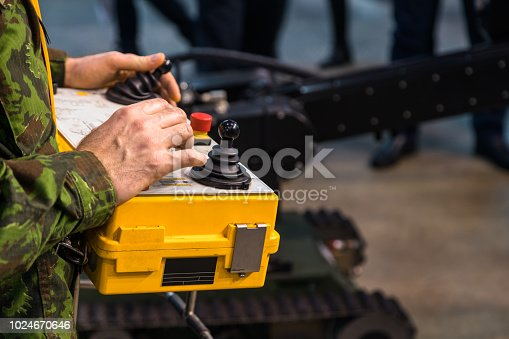 Mans hands in military jacket operating machine. Industry, industrial concept