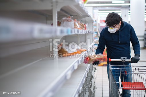 Man's hands wearing rubber gloves holding product in a supermarket during an epidemic of an infectious disease