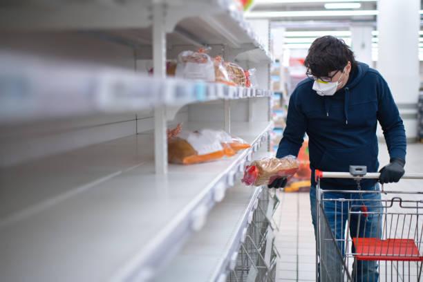 manos de hombre en guantes de protección buscando pan en estantes vacíos en una tienda de comestibles - desierto fotografías e imágenes de stock