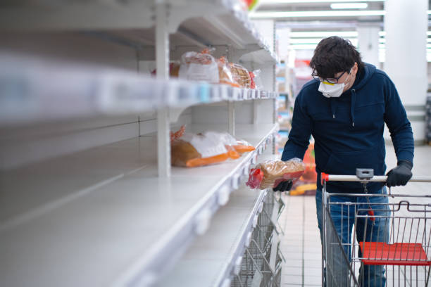 Männerhände in Schutzhandschuhen suchen Brot in leeren Regalen in einem Lebensmittelgeschäft – Foto
