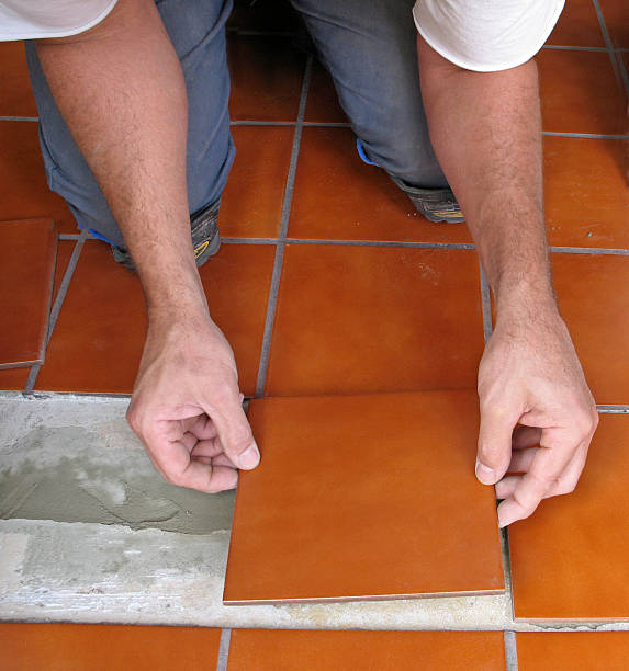 Man's hands laying ceramic tile stock photo